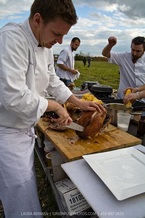 A chef slicing a turkey at an outdoor farm feast.