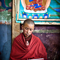 A child monk prays during morning devotions with the painting of Buddha behind him.