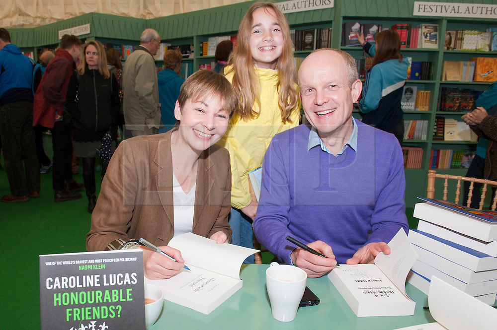 © London News Pictures. 29/05/2015. Hay-on-Wye, Powys, Wales, UK. Caroline Lucas, Scarlett Simms 11 (daughter of Andrew) and Andrew Simms sign copies  of their books  at the Hay Festival 2015. Photo credit: Graham M. Lawrence/LNP.