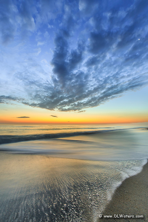 Clouds and streaks of bubbles in the surf lead the viewer's eye to the yellow glow before the sunrise on the horizon.