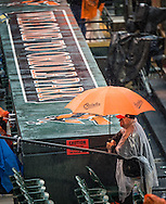 A fan huddles under an umbrella during a rain delay on opening day at Oriole Park at Camden Yards in Baltimore, Monday, April 4, 2016.  The Baltimore Orioles defeated the Minnesota Twins 3-2.