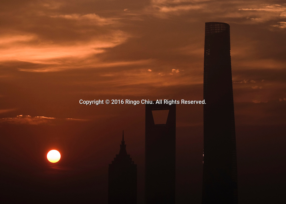 View of the Pudong skyline as seen at sunrise from the Meridien Hotel in Shanghai, China, Shanghai is the most populous city in China and the most populous city proper in the world. It is one of the four direct-controlled municipalities of China, with a population of more than 24 million as of 2014. It is a global financial centre, and a transport hub with the world's busiest container port. Located in the Yangtze River Delta in East China, Shanghai sits on the south edge of the mouth of the Yangtze in the middle portion of the Chinese coast. The municipality borders the provinces of Jiangsu and Zhejiang to the north, south and west, and is bounded to the east by the East China Sea. A major administrative, shipping, and trading town, Shanghai grew in importance in the 19th century due to trade and recognition of its favourable port location and economic potential. The city was one of five forced open to foreign trade following the British victory over China in the First Opium War while the subsequent 1842 Treaty of Nanking and 1844 Treaty of Whampoa allowed the establishment of the Shanghai International Settlement and the French Concession. The city then flourished as a center of commerce between China and other parts of the world (predominantly Western countries), and became the primary financial hub of the Asia-Pacific region in the 1930s. However, with the Communist Party takeover of the mainland in 1949, trade was limited to socialist countries, and the city's global influence declined. In the 1990s, the economic reforms introduced by Deng Xiaoping resulted in an intense re-development of the city, aiding the return of finance and foreign investment to the city. Shanghai has been described as the &quot;showpiece&quot; of the booming economy of mainland China; renowned for its Lujiazui skyline, museums and historic buildings, such as those along The Bund, the City God Temple and the Yu Garden.(Photo by Ringo Chiu/PHOTOFORMULA.com)<br /> <br /> Usage Notes: This content is intended fo