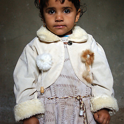 Fayoume, Egypt: Wesam, 3, a neighbor of Wael, 16, who lives in Hamidia village in Fayoume, Egypt wears a rabbit fur decoration on her jacket that came from one of Wael's rabbits ,  part of a telefood program funded by FAO December 7, 2005.   The project has given him enough money to pay for school and buy goats for his family. .(Photo Ami Vitale)