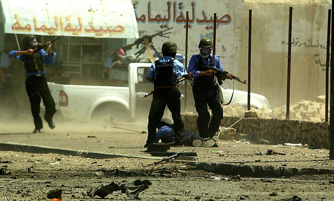 Iraqi Police exchange gunfire with Anti Iraqi Forces moments after a suicide car bomb exploded in front of them on August 10, 2006 at an intersection they were working in Tameem, Ramadi, Iraq. The soldiers from Bravo Company 2-6 Infantry, Task Force 1-35 from Baumholder Germany, were performing a routine patrol at an intersection in Tameem, a suburb of Ar Ramadi when a suicide car bomb exploded about twenty five meters in front of the patrol. Initial reports indicated that two were killed (one civilian and the bomber) and four were wounded (one Iraqi Police Officer and three civilians). Immediately after the explosion, Soldiers of Bravo Company cordoned off the area, treated and evacuated the wounded and maintained security until an Explosive Ordinance Disposal team (EOD) arrived to clear the area.  One civilian died of wounds at the treatment facility.  While EOD was on scene, the patrol took small arms fire from outside of the cordon.  EOD recovered one 110mm artillery round and three 115mm rounds that were believed to be connected with detonation wires from the dashboard of the vehicle. — © TSgt Jeremy Lock/