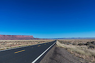 The open road on US 89 in northern Arizona by the Vermilion Cliffs, with a waxing quarter Moon in the blue sky.