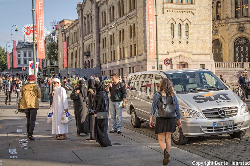 Mann med tre kvinner i niqab, Karl Johans gate, ved Stortinget i Oslo.