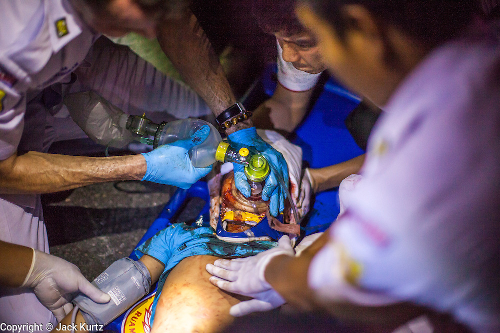 """10 NOVEMBER 2012 - BANGKOK, THAILAND: A Ruamkatanyu Foundation medical team tries to save the life of a boy hit by a vehicle near the Klong Toey slum in Bangkok. The child had severe head injuries and died at the scene. The Ruamkatanyu Foundation was started more than 60 years ago as a charitable organisation that collected the dead and transported them to the nearest facility. Crews sometimes found that the person they had been called to collect wasn't dead, and they were called upon to provide emergency medical care. That's how the foundation medical and rescue service was started. The foundation has 7,000 volunteers nationwide and along with the larger Poh Teck Tung Foundation, is one of the two largest rescue services in the country. The volunteer crews were once dubbed Bangkok's """"Body Snatchers"""" but they do much more than that now.    PHOTO BY JACK KURTZ"""