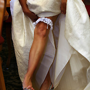 A bride slips on her garter while readying for the upcoming ceremony.