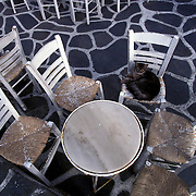 A cat finds comfort on an outdoor cafe chair in Santorini, Greece.