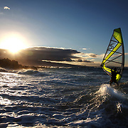 A windsurfer rides a wave at Hookipa Beach on the north shore of Maui.  In winter Hookipa Beach is the site of several world championship contests.