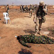 A U.S. Army 3rd Division soldier pauses to look   at the body of a slain Iraqi soldier April 5, 2003 after an assault on the Baghdad International Airport. U.S. and Iraqi forces exchanged heavy fire throughout the day as they battled for control of the strategic facility.