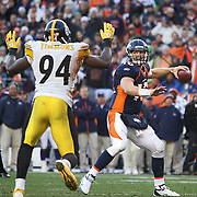 SHOT 1/8/12 4:52:57 PM - The Denver Broncos Tim Tebow #15 looks to pass as Lawrence Timmons #94 of the Pittsburgh Steelers closes in during their AFC Wildcard game at Sports Authority Field at Mile High on Sunday January 8, 2012.  (Photo by Marc Piscotty / © 2012)