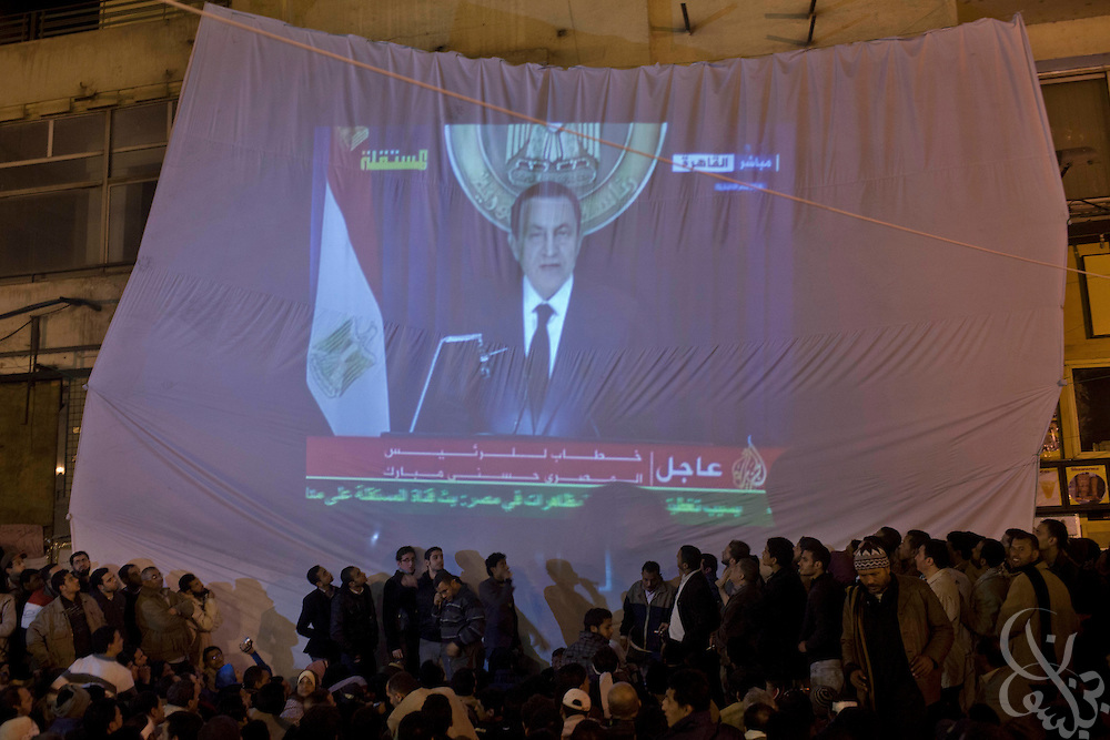 "Egyptian protesters watch a live televised speech by President Hosni Mubarak February 01, 2011 in Central Cairo's Tahrir, or ""Liberation"" square. Mubarak announced he would not seek re-election in elections later this year and would immediately enact reforms in the constitution."