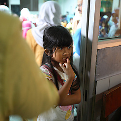 A young girl watches as other girls are circumcised in Bandung, Indonesia on April 23, 2006. The families of 248 girls were given money to have their children circumcised in a mass circumcision celebration timed to honour the Prophet Mohammed's birthday. While religion was the main reason for circumcisions, it is believed by some locals that a girl who is not circumcised would have unclean genitals after she urinates which could lead to cervical cancer. It is also believed if one prays with unclean genitals their prayer won't be heard. The practitioners used scissors to cut the hood and tip of the clitoris. The World Health Organization has deemed the ritual unnecessary and condemns such practices.