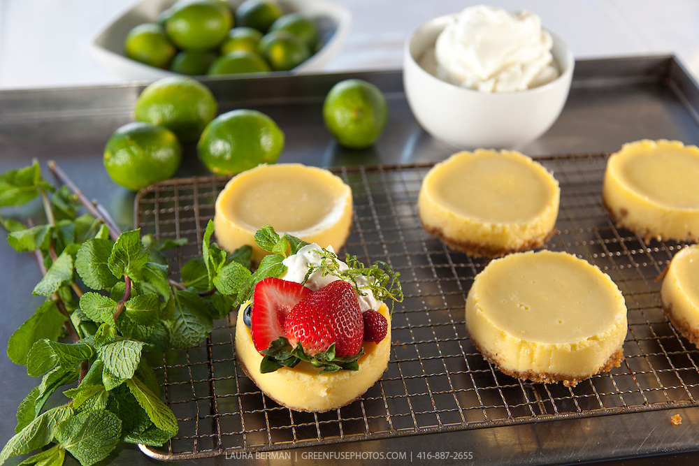Preparation of Key Lime tarts topped with whipped cream, fresh strawberries and mint leaves. Food styled by Laura Prentice.