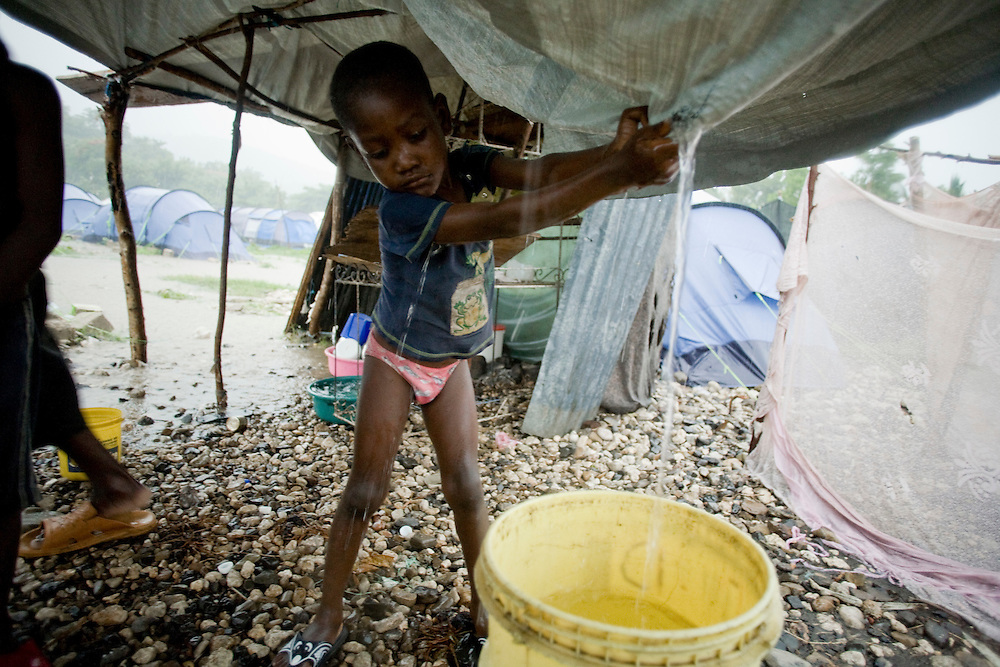 Sourin Nicholene, age 5, drains water from a hole in the tarp roof into a bucket for drinking water. The family stands under a tarp shelter during the rain in their flooding camp. The Nicholene family was displaced by the January earthquake.