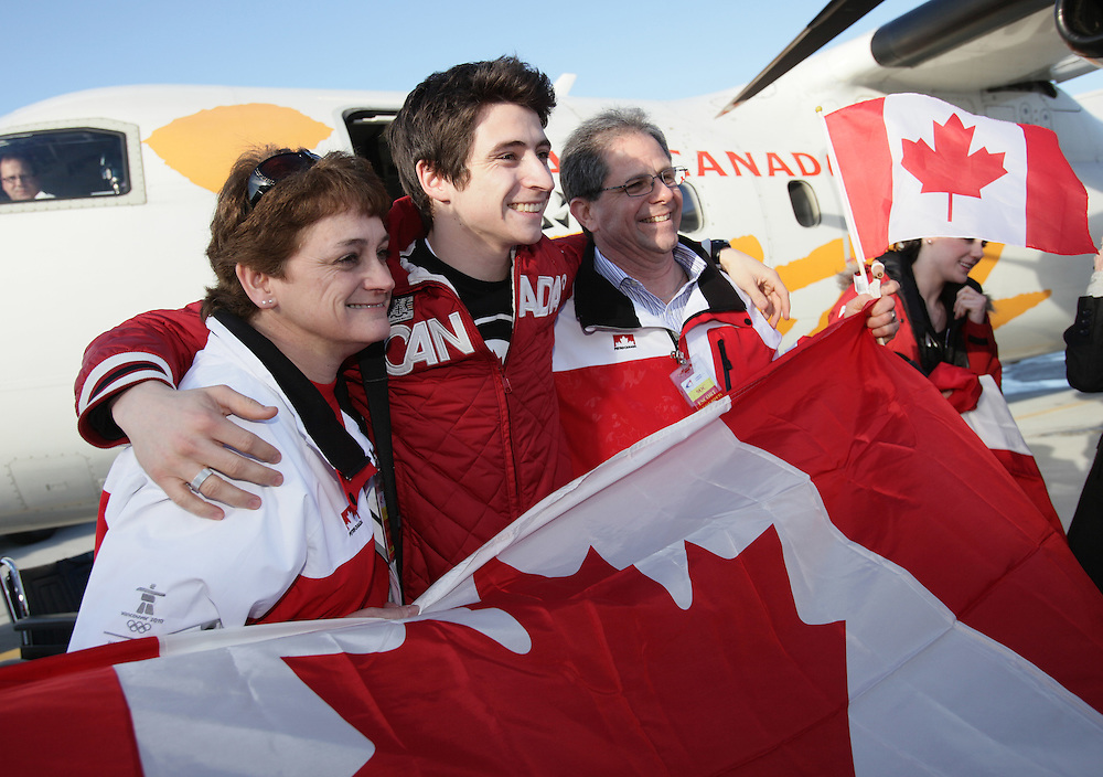 London, Ontario ---02/03/10--- Olympic Gold Medalist in Ice dance Scott Moir gets poses for pictures with his parents Alma and Joe as he and partner Tessa Virtue arrive at the airport in London, Ontario, March 2, 2010.<br /> CP PHOTO/'GEOFF ROBINS