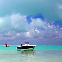 Small boats on green tropical waters under a partly cloudy blue sky