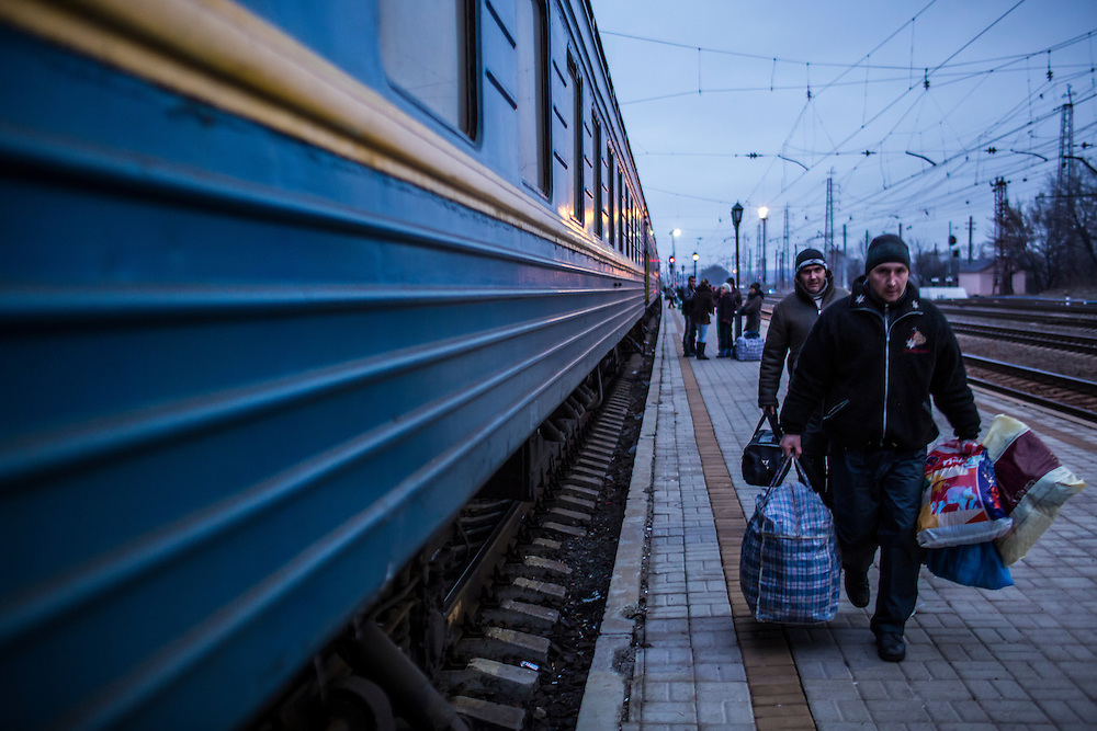 SLOVYANSK, UKRAINE - FEBRUARY 7, 2015: People displaced by fighting in the town of Debaltseve carry their belongings at the train station in Slovyansk, Ukraine. Many civilians have been evacuated from Debaltseve and brought to Slovyansk, where they are either given a free onward ticket or housed in a train until they can make further plans. CREDIT: Brendan Hoffman for The New York Times
