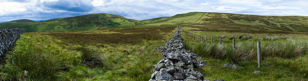 The Schil, Yetholm, Scottish Borders, UK. 22nd July 2015. Looking north west towards Black Hag (549m) and The Curr (564m) along the Scottish English border (Scotland to the left of the fence line).