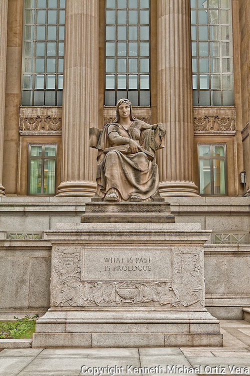 "A female statue in front of the National Archives building with a statement that says, ""What is Past is Prologue."""