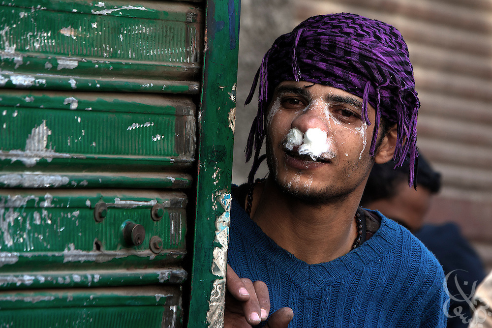 An Egyptian protestor uses cotton balls dipped in vinegar as defense against tear gas fired by security forces during demonstrations November 21, 2011 near Tahrir square  in central Cairo, Egypt. Thousands of protestors demanding the military cede power to a civilian government authority clashed with Egyptian security forces for a third straight day in Cairo, with hundreds injured and at least 24 protestors killed.  (Photo by Scott Nelson)