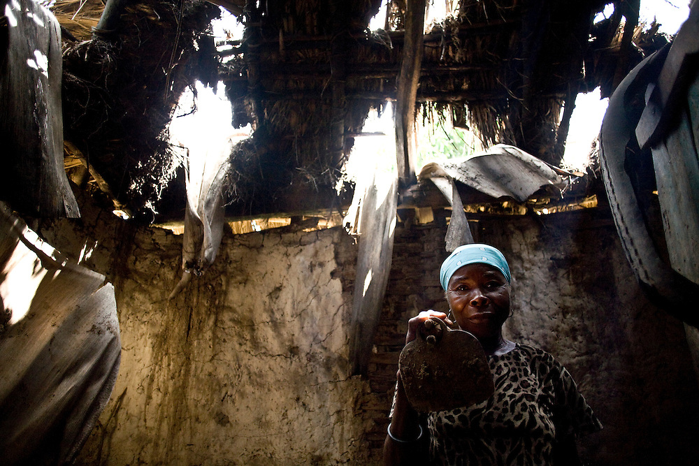 A woman stands in her home with a partially collapsing roof.