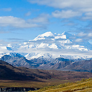 "Denali (formerly known as Mount McKinley) rises to 20,310 feet elevation (6191 m) along Denali National Park Road near Eielson Visitor Center, Alaska, USA. Denali is the highest mountain peak in North America, and measured from base to peak, it is earth's tallest mountain on land. Denali is only visible 1 out of 3 days. Rain falls as light showers or drizzle for half of summer days. The earliest shuttle bus doesn't reach Denali views until mid morning. The least cloudy time is early morning, which suggests overnight tenting at Wonder Lake to best see the mountain. Denali is a granitic pluton uplifted by tectonic pressure while erosion has simultaneously stripped away the softer sedimentary rock above and around it. The native Athabaskan name ""Denali"" replaced ""Mount McKinley"" in 2015. Published in ""Light Travel: Photography on the Go"" by Tom Dempsey 2009, 2010."