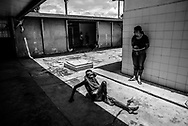 BARQUISIMETO, VENEZUELA - AUGUST 25, 2016: Schizophrenic patient, <br /> Alegr&iacute;a Flores, 72, crawls on the floor with her clothes put on wrong. She constantly takes off her clothes and puts each item around her neck like scarves. She does not have all of the medicines that she needs to control her disorder, and regularly urinates and defecates on herself. Her skin is infected with scabies. The economic crisis that has left Venezuela with little hard currency has also severely affected its public health system, crippling hospitals like El Pampero Psychiatric Hospital by leaving it without the resources it needs to take care of patients living there, the majority of whom, like Alegr&iacute;a, have been abandoned by their families and rely completely on the state to meet their basic needs. The hospital does not even have basic hygiene or cleaning supplies.  There is no soap, no shampoo, no tooth paste, no toilet paper.  Patients relieve themselves in the common areas and patio area, and clean themselves only with water. Nearly every patient is infected with scabies because they do not have the resources to bathe properly or to have their threadbare, misfitted clothes washed as often as needed. To make matters worse, the hospital only has running water a few hours a day.  PHOTO: Meridith Kohut for The New York Times