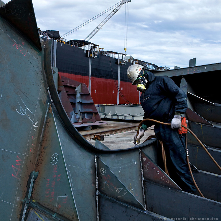 Worker gliding the plate's surface before applying painting on pieces that will be placed on a ship that is under construction.