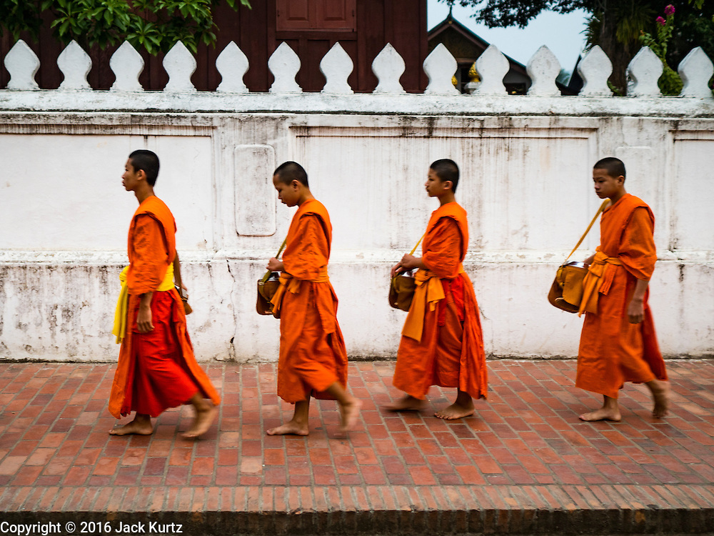 """11 MARCH 2016 - LUANG PRABANG, LAOS:   Buddhist monks walk down the main street of Luang Prabang during the morning tak bat. Luang Prabang was named a UNESCO World Heritage Site in 1995. The move saved the city's colonial architecture but the explosion of mass tourism has taken a toll on the city's soul. According to one recent study, a small plot of land that sold for $8,000 three years ago now goes for $120,000. Many longtime residents are selling their homes and moving to small developments around the city. The old homes are then converted to guesthouses, restaurants and spas. The city is famous for the morning """"tak bat,"""" or monks' morning alms rounds. Every morning hundreds of Buddhist monks come out before dawn and walk in a silent procession through the city accepting alms from residents. Now, most of the people presenting alms to the monks are tourists, since so many Lao people have moved outside of the city center. About 50,000 people are thought to live in the Luang Prabang area, the city received more than 530,000 tourists in 2014.     PHOTO BY JACK KURTZ"""