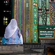 A woman kept outside of the Shaw-i-Hamdan Shrine.