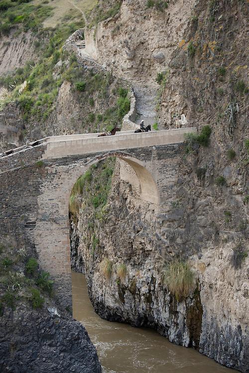 South America,Peru, Colca Canyon, people riding over stone bridge