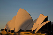 Tourists walk on the forecourt of the Sydney Opera House in late afternoon winter light.