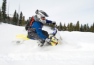 NEWS&GUIDE PHOTO / PRICE CHAMBERS.With the front ski buried in powder, Randy Schrauder carves turns through a meadow near Phillip's Canyon on Friday. While a snowbike lacks the stability of a wheel's gyroscopic motion, the snowmobile-like track provides ample contact with the surface as you wind through the gears.