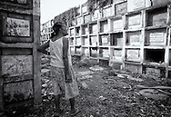 Elderly woman and resident of Navotas cemetery wanders among the graves and praying for all those buried there.