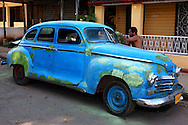 Sanding an old blue car in Boyeros, south Havana, Cuba.
