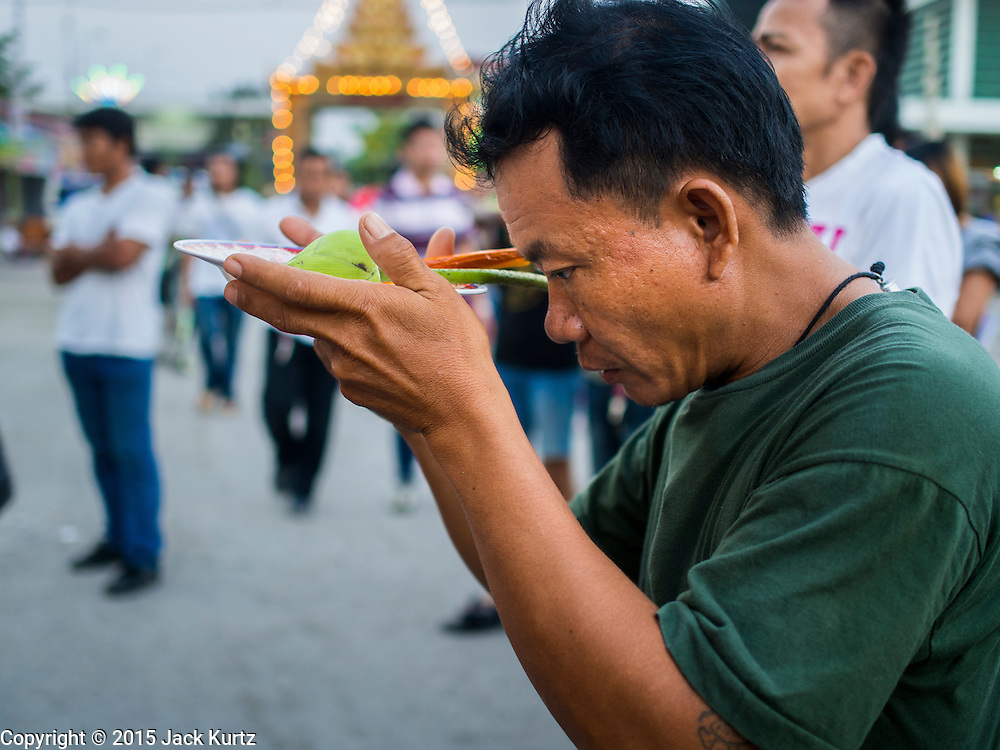 "07 MARCH 2015 - NAKHON CHAI SI, NAKHON PATHOM, THAILAND:  A man prays at the Wat Bang Phra tattoo festival. Wat Bang Phra is the best known ""Sak Yant"" tattoo temple in Thailand. It's located in Nakhon Pathom province, about 40 miles from Bangkok. The tattoos are given with hollow stainless steel needles and are thought to possess magical powers of protection. The tattoos, which are given by Buddhist monks, are popular with soldiers, policeman and gangsters, people who generally live in harm's way. The tattoo must be activated to remain powerful and the annual Wai Khru Ceremony (tattoo festival) at the temple draws thousands of devotees who come to the temple to activate or renew the tattoos. People go into trance like states and then assume the personality of their tattoo, so people with tiger tattoos assume the personality of a tiger, people with monkey tattoos take on the personality of a monkey and so on. In recent years the tattoo festival has become popular with tourists who make the trip to Nakorn Pathom province to see a side of ""exotic"" Thailand.  PHOTO BY JACK KURTZ"