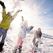 three girls through snow up into the air to celebrate winter in montana