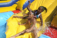 Addison Howell and Madison Armstrong slide into water during the Juneteenth Celebration in Oxford, Miss. on Saturday, June 19, 2010.