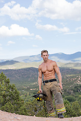 shirtless muscular fireman outdoors on a mountain top in New Mexico