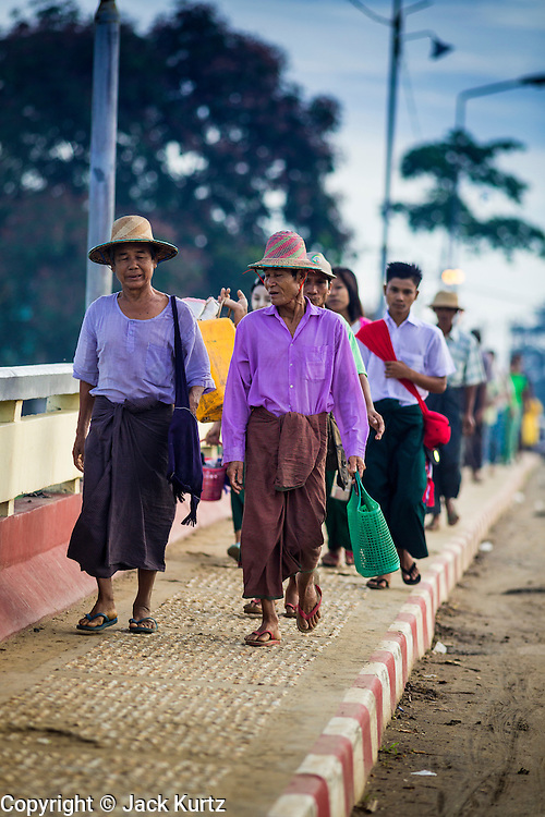 06 JUNE 2014 - IRRAWADDY DELTA,  AYEYARWADY REGION, MYANMAR: Burmese walk into Pantanaw, a town in the Irrawaddy Delta (or Ayeyarwady Delta) in Myanmar. The region is Myanmar's largest rice producer, so its infrastructure of road transportation has been greatly developed during the 1990s and 2000s. Two thirds of the total arable land is under rice cultivation with a yield of about 2,000-2,500 kg per hectare. FIshing and aquaculture are also important economically. Because of the number of rivers and canals that crisscross the Delta, steamship service is widely available.   PHOTO BY JACK KURTZ
