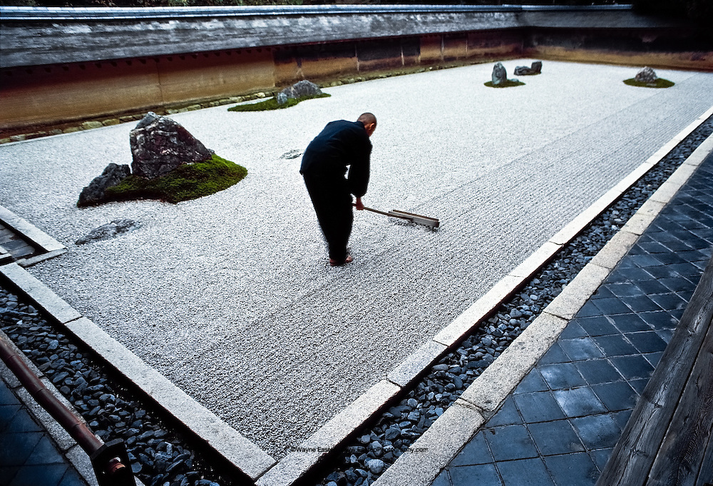 Seventeen year old Tadaichi Iwahashi, apprentice monk, rakes the zen garden at Ryoanji, a Zen temple in Kyoto.  The rock and sand garden embodies Japanese aesthetics-nature at its simplest, art at  its most refined. Japan