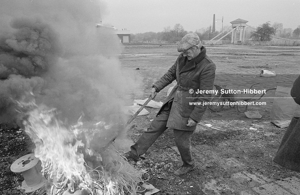 Burning scrap wiring to burn off the plastic, and recover the metal inside, in the Gorbals, Glasgow, Scotland, November 1993. In the background is the Mr. Happy character from 'Glasgow'S Miles Better' advertising campaign.