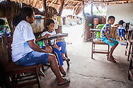 Joina Brito, 36, gives a lesson at the school set up in a shack to the few children of the oasis. She teaches 11 children, all being part of her family. She is been teaching the children for 16 years, when she replaced her mother. In Queimada dos Britos lives around 60 people. In the oasis everybody is a relative, cousins intermarrying frequently as a normal course. The legend says that the founder Manuel Brito, when running away from home due to a drought that was scorching his homeland, he ended up settling down in the only non-sandy portion of the Lençois.