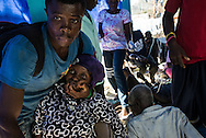 RENDEL, HAITI - OCTOBER 12, 2016:  An unresponsive  woman exhibiting symptoms of cholera is stabilized as her eyes roll back in her head and she shakes uncontrollably at the small clinic in Rendel, Haiti - which is overflowing with Cholera patients, and more keep coming. For days, aid groups and officials have warned of a coming Cholera outbreak that could affect as many as 500,000 Haitians.  The town of Rendel and its surroundings, which once sheltered 25,000 people, is an epicenter of the coming disaster. Heroic nurses care for patients splayed on the floor like silent rag dolls, some resting atop the improvised stretchers they arrived on. Patients vomit and defecate on the floor or into small yellow buckets, too sick to leave their stifling confines. The smell of bile and excrement stings the nostrils. PHOTO: Meridith Kohut for The New York Times