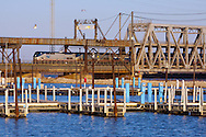 Amtrak's westbound Southwest Chief crosses BNSF's massive swing bridge over the Mississippi River at Ft. Madison, IA. The harbor in the foreground is empty on this cool spring day, but soon, will be full of summertime boaters.