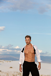 Hot man in an open tuxedo shirt on a sand dune in New Mexico