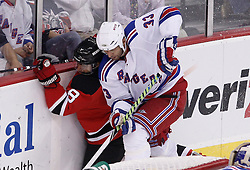 Oct 5, 2009; Newark, NJ, USA; New York Rangers defenseman Michal Rozsival (33) hits New Jersey Devils right wing Dainius Zubrus (8) during the third period at the Prudential Center. The Rangers defeated the Devils 3-2.