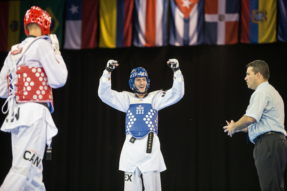 Gold medalist Saul Gutierrez (R) of Mexico celebrates his victory over  Maxine Potvin of Canada during their gold medal contest in the men's Taekwondo -68kg division of at the 2015 Pan American Games in Toronto, Canada, July 20,  2015.  AFP PHOTO/GEOFF ROBINS
